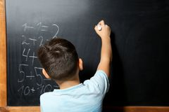 Little child with chalk doing math. At blackboard royalty free stock photos