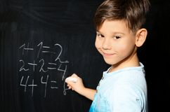 Little child with chalk doing math. At blackboard stock photo