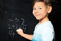 Little child with chalk doing math. At blackboard stock photography
