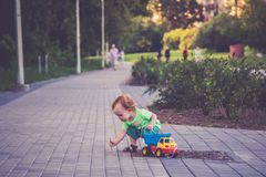 Little child in a city street. Walking area playing with a car stock photography