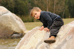 Little child climbing rock. Agile little child climbing white rock Stock Images