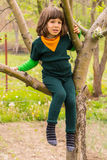Little child climbing in the tree. Little child boy in green wool clothes climbing in the tree Royalty Free Stock Image