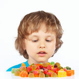 Little child with colored jelly candies on white background Royalty Free Stock Photo