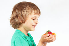Little child with colored sweets and jelly candies on white background Royalty Free Stock Photography