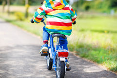 Little child in colorful clothes on bicycle Stock Photos