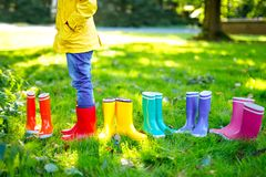 Little child in colorful rain boots. Close-up of school or preschool legs of kid boy or girl in different rubber boots. Jeans and jackets. Footwear for rainy stock photos