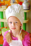 Little child cook portrait. Indoor head portrait of a cute little Caucasian girl child cook with flour and chocolate in her pretty face wearing a white chef's royalty free stock image