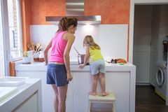 Little child cooking with mother supervising Royalty Free Stock Photos