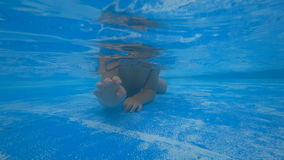 Little child crawling on the bottom of swimming pool stock video