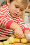 Little child cutting potatoes Royalty Free Stock Photos