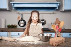 Little child daughter girl is helping her mother in the kitchen to make bakery, cookies. She has a flood all over her. Face. Fun cooking, homemade food, little royalty free stock image