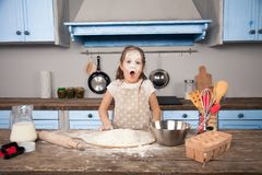 Little child daughter girl is helping her mother in the kitchen to make bakery, cookies. She has a flood all over her. Face. Fun cooking, homemade food, little royalty free stock photo