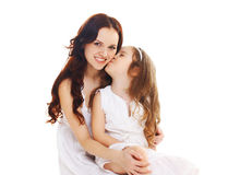 Little child daughter kissing happy mother on white. Background Royalty Free Stock Image