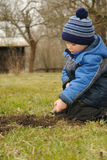 Working in garden. Little child deeping a pit for new plant, working in the garden Royalty Free Stock Images