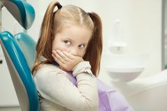 Little child at dentist office in comfortable chair. Little child with wide open green eyes and ginger hair sits at dentist office in comfortable leather chair Stock Photography