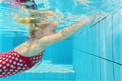 Little child diving underwater in the pool royalty free stock images