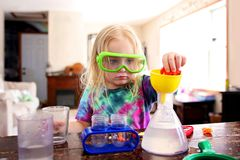 Little Child Doing a Science Experiement with Toy Scientist Kit royalty free stock images