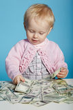 Little child with dollars on table Royalty Free Stock Photos