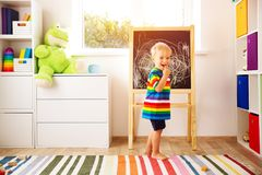 Little child drawing on the blackboard. Boy standing in the room with chalkboard stock photos