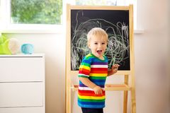 Little child drawing on the blackboard. Boy standing in the room with chalkboard stock images