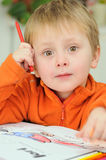 Little child with drawing book. Little child drawing with colourful crayon in painting book stock photography