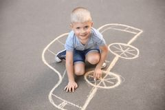 Little child drawing car with chalk. On asphalt royalty free stock photography