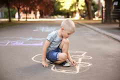 Little child drawing car with chalk. On asphalt royalty free stock image