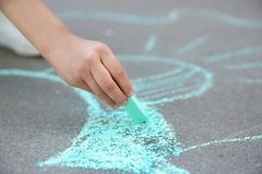 Little child drawing with chalk on asphalt Stock Image