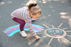 Little child drawing with colorful chalk. On asphalt royalty free stock photo