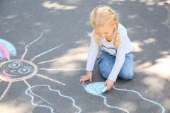 Little child drawing with colorful chalk. On asphalt stock image