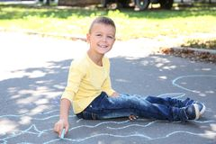 Little child drawing with colorful chalk. On asphalt stock photos