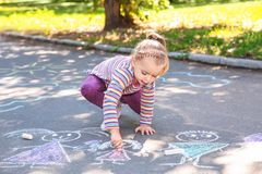 Little child drawing with colorful chalk. On asphalt royalty free stock images