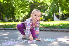 Little child drawing with colorful chalk. On asphalt royalty free stock photos