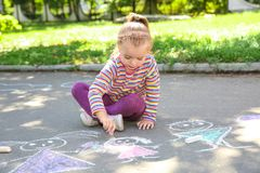 Little child drawing with colorful chalk. On asphalt stock photography