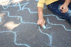 Little child drawing with colorful chalk on asphalt. Closeup stock photography