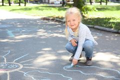 Little child drawing with colorful chalk on asphalt. Space for text royalty free stock photos