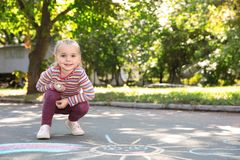 Little child drawing with colorful chalk on asphalt. Space for text stock photo