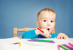 Little child drawing on the paper. Boy sitting on the chair at table with pencils stock photo