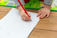 Little child drawing with pencil on white paper Royalty Free Stock Photos