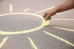 Little child drawing sun with chalk Stock Images