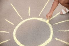Little child drawing sun with chalk Stock Photo