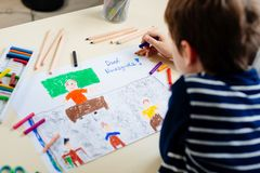 Little child draws a pastel drawing of his teacher in school class. Teachers day in Polish language stock photography