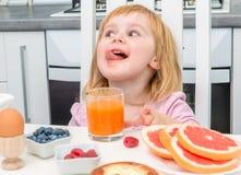 Little child drinking juice stock image