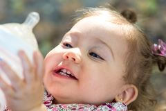 Little child drinking milk from baby bottle outdoors. royalty free stock photo
