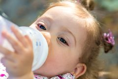 Little child drinking milk from baby bottle outdoors stock photos