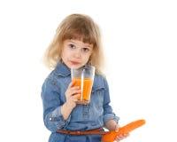 Little child drinks carrot juice. Stock Photos