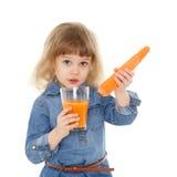 Little child drinks carrot juice. Stock Photo