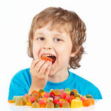 Little child eating candies on white background Royalty Free Stock Photography