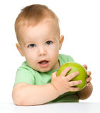 Little child is eating green apple Stock Photo