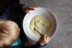 Little child eating noodle milk soup stock photos